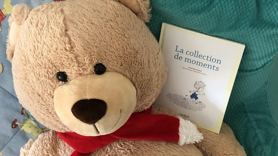 Le livre est posé sur l'épaule d'un gros ours en peluche et un coussin turquoise.