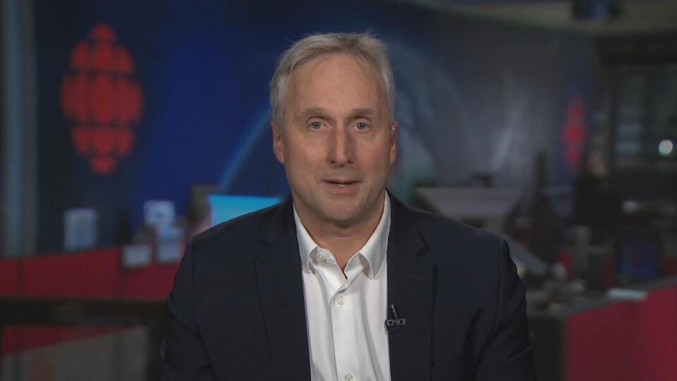 Un homme aux cheveux blanc-gris, en veston, assis dans un studio de télévision.