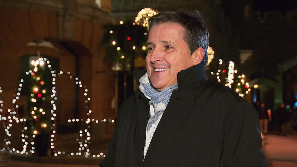Jean Pitole à l'extérieur avec un manteau noir et un foulard bleu. Il sourit.