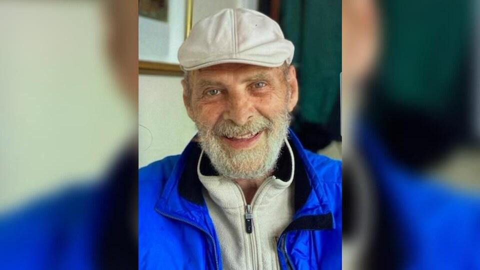 Jean Pleau a les cheveux gris, des yeux pers et une barbe grise.