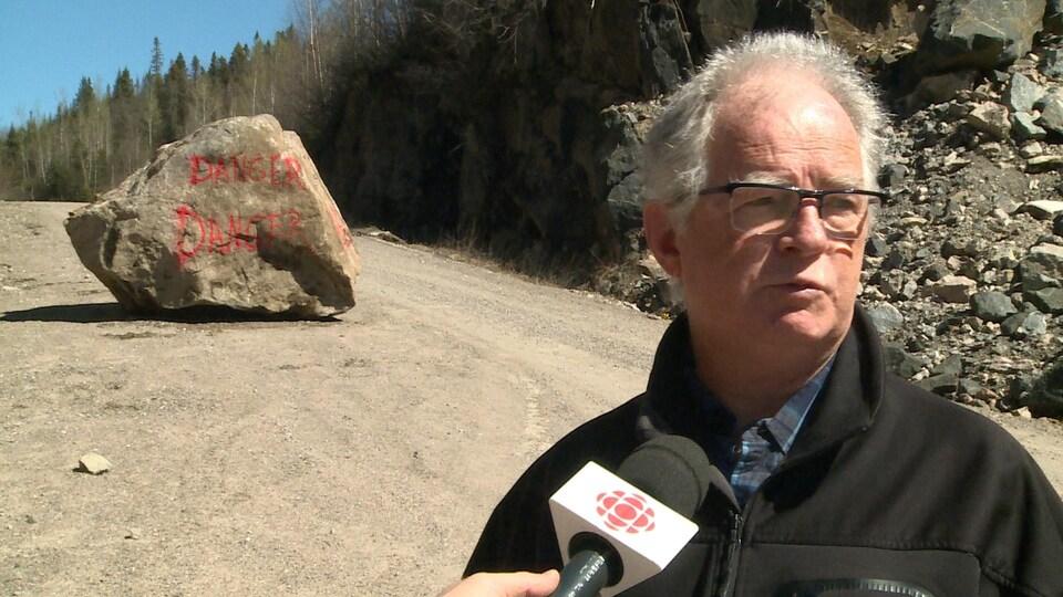 Un homme âgé debout dans le chemin avec une énorme roche dans l'arrière plan.