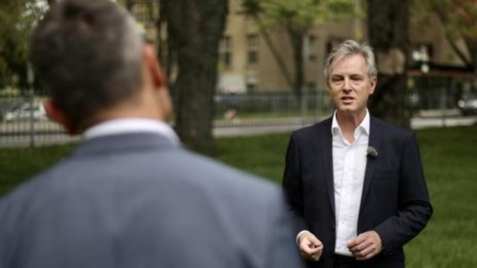Jean Rousseau accorde une entrevue à l'animateur du Téléjournal Québec, Bruno Savard, à l'extérieur.