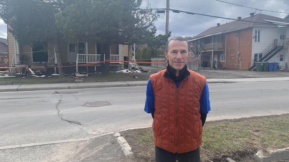 Jean-Sébastien Lavoie se tient devant l'immeuble lourdement endommagé par les flammes.