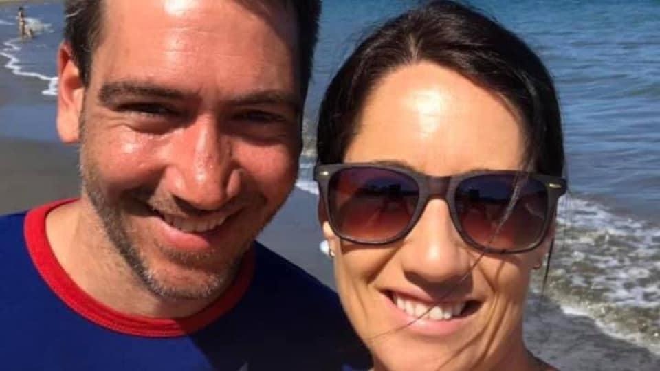 Le couple sourit, sur la plage.