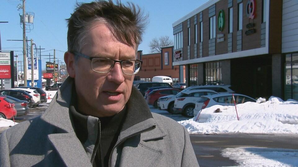 Un homme portant des lunettes debout devant des commerces