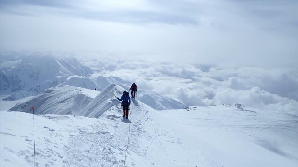 Deux hommes marchent le long d'une crête de montagne.