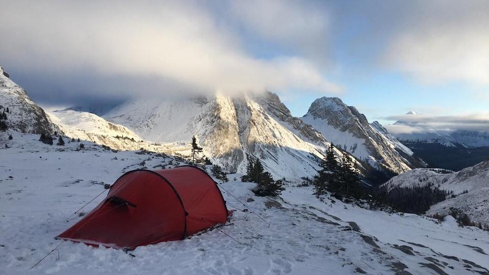 Une tente rouge au bord du montagne qui fait face à la vue de plusieurs montagnes.