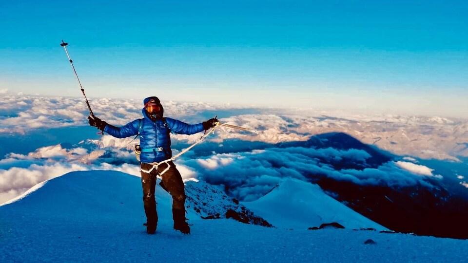 Jean-François Dupras se tient au haut de la montagne avec une vue sur les nuages et tient en l'air ses deux bâtons.