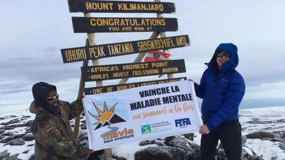 Deux hommes se tiennent au sommet du Kilimandjaro et tiennent la bannière du projet : Vaincre la maladie mentale, un sommet à la fois.