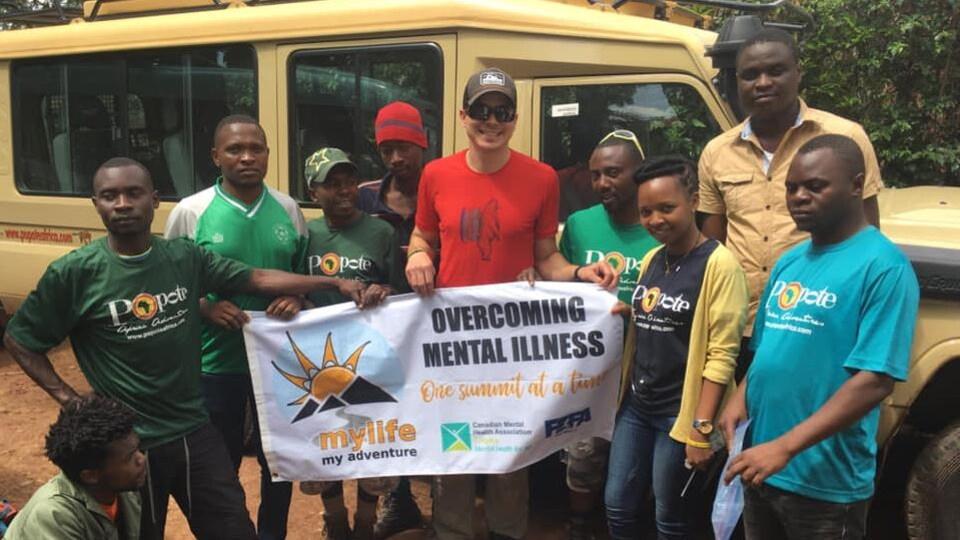 Plusieurs personnes entourent Jean-François Dupras et tiennent toutes ensemble la bannière du projet Overcoming Mental Illness, One summit at a time.