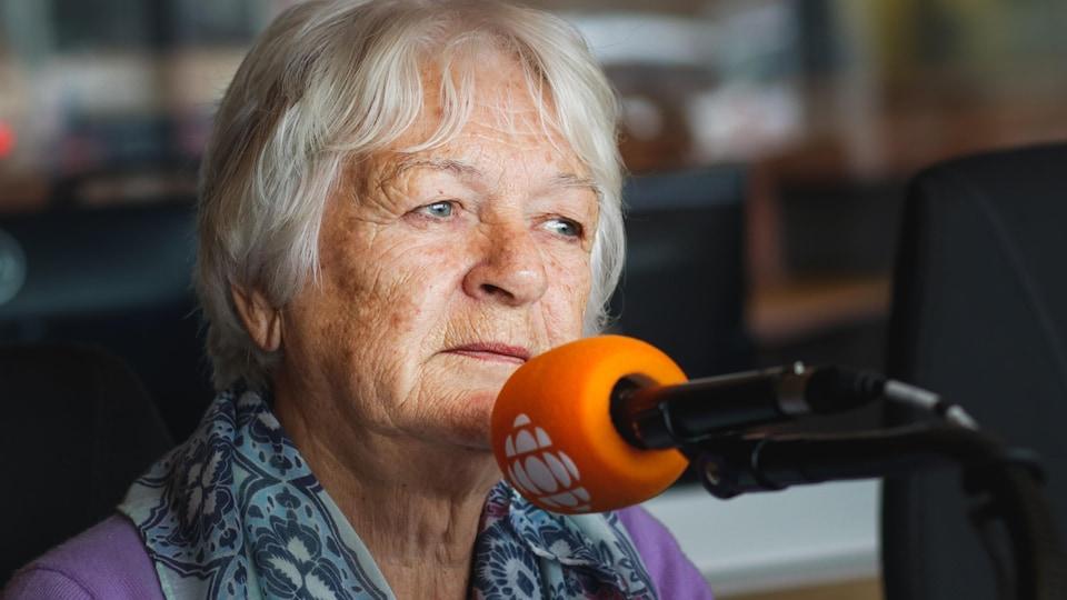 Une femme qui parle à un micro.
