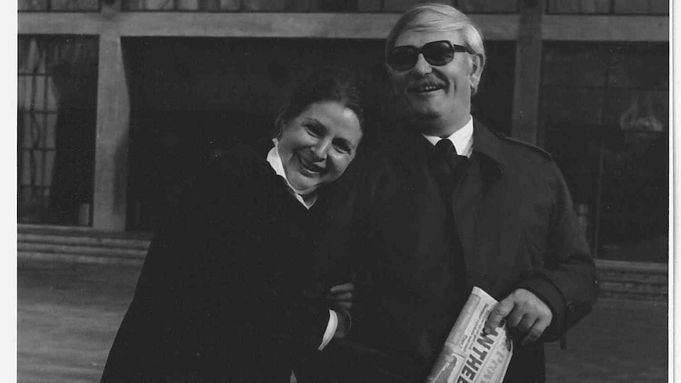 Jeanne Baillaut au bras de Jacques  Baillaut tenant un journal, souriant à la caméra.