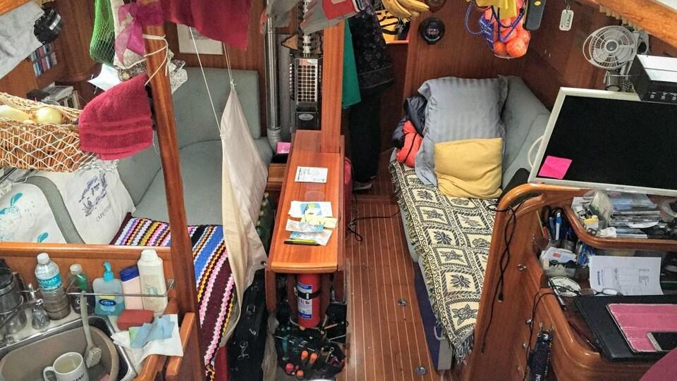 L'intérieur du voilier a deux banquettes, un évier, un écran d'ordinateur et des oranges dans un sac qui pendent du plafond.