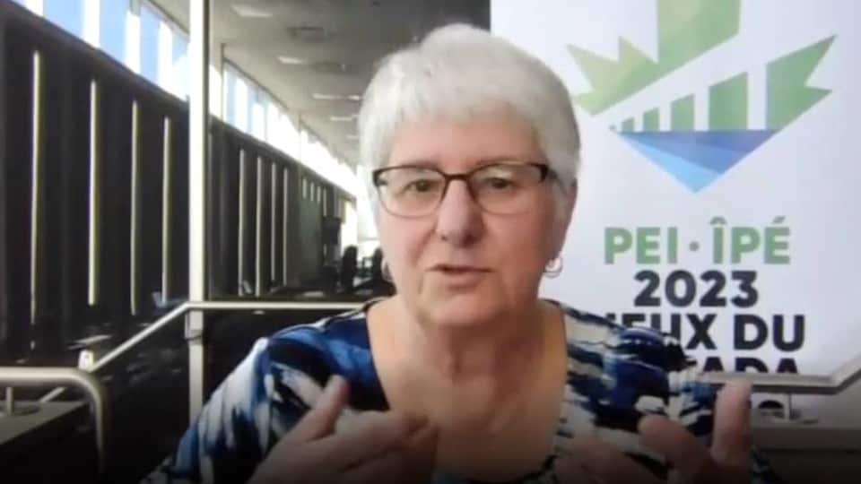 Jeannette Arsenault en entrevue par webcam devant une affiche du logo des Jeux du Canada.