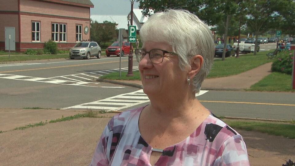 Une femme souriante à l'extérieur, près d'un espace commercial.
