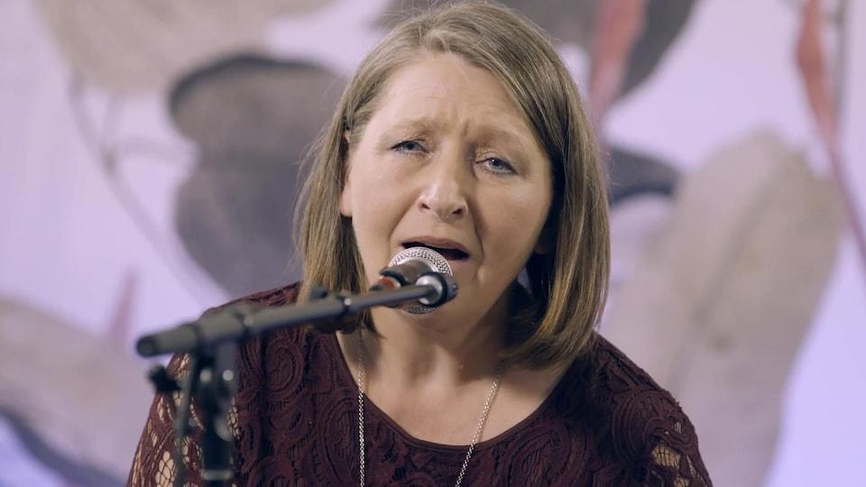 L'auteure-compositrice-interprète Jeannine Guyot chante au micro.