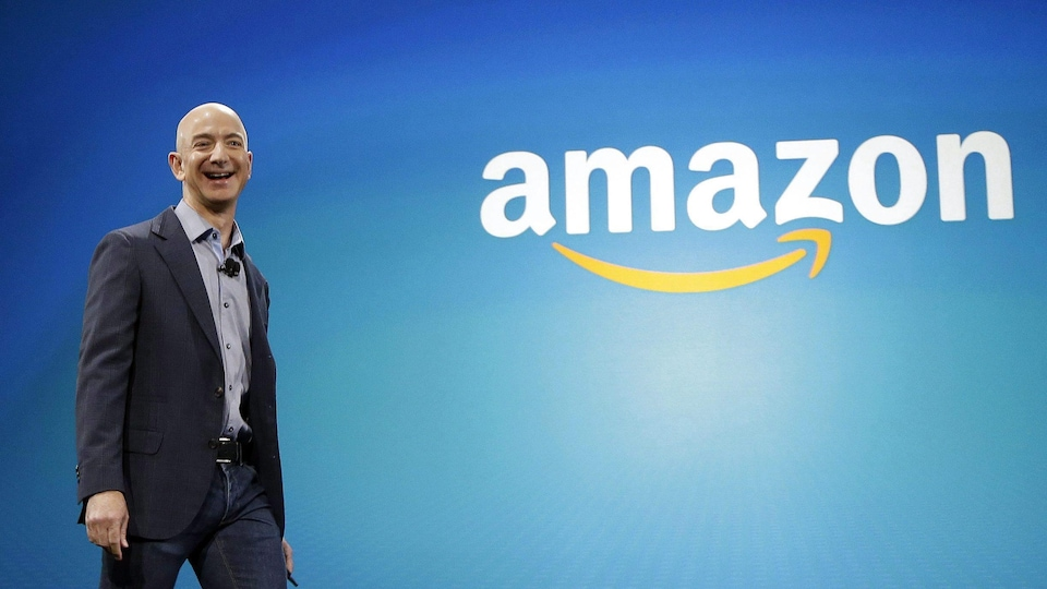 L'homme est debout et sourit. Derrière lui se trouve un grand mur sur lequel on voit le logo d'Amazon.