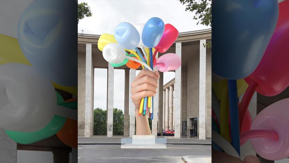 Oeuvre d'art représentant une main qui tient des tulipes géantes en ballons gonflables de toutes les couleurs