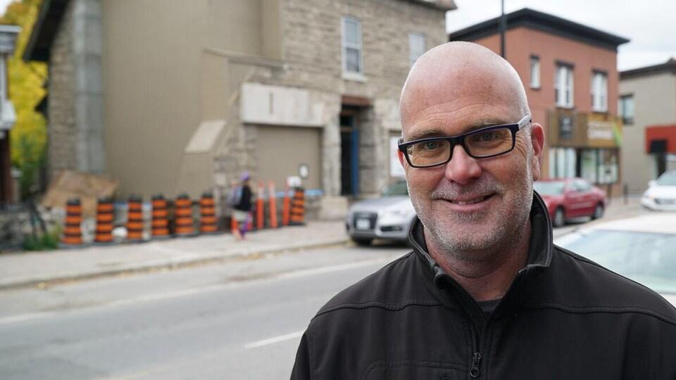 Jeff Leiper pose pour la caméra devant une maison partiellement effondrée.