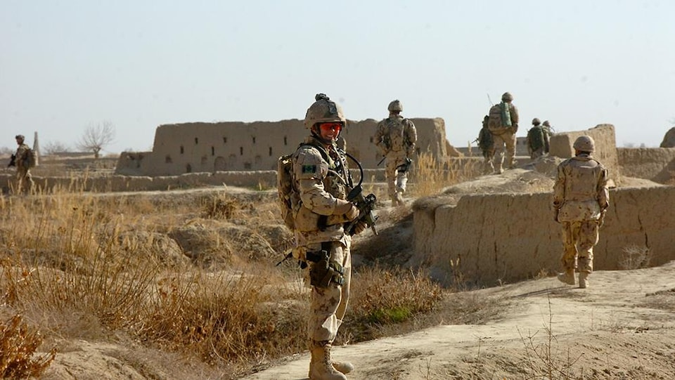 Jennie Carignan en uniforme militaire dans une zone désertique, en Afghanistan.