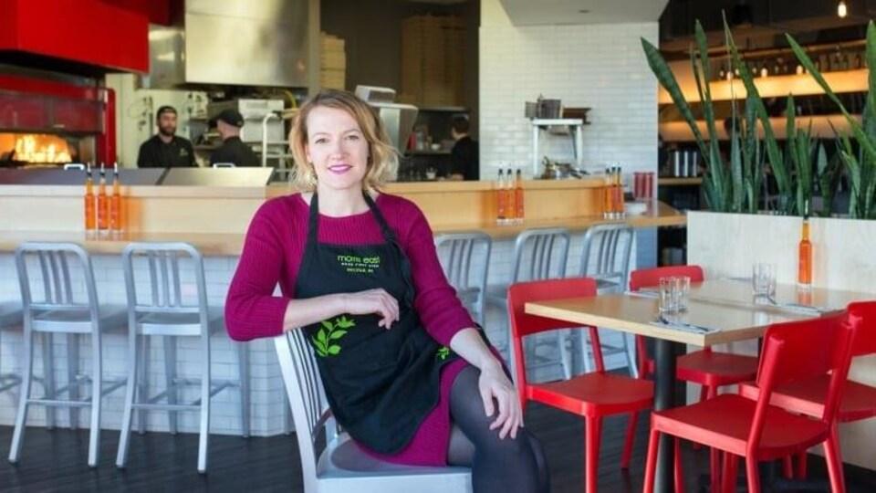 Jennie Dobbs, jeune femme assise avec un tablier dans un restaurant de pizza chic.