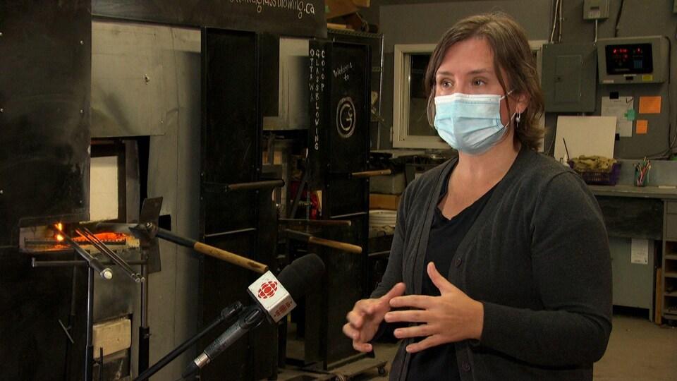 Une souffleuse de verre, masque sur le visage, donne des explications dans l'atelier de la coopérative.
