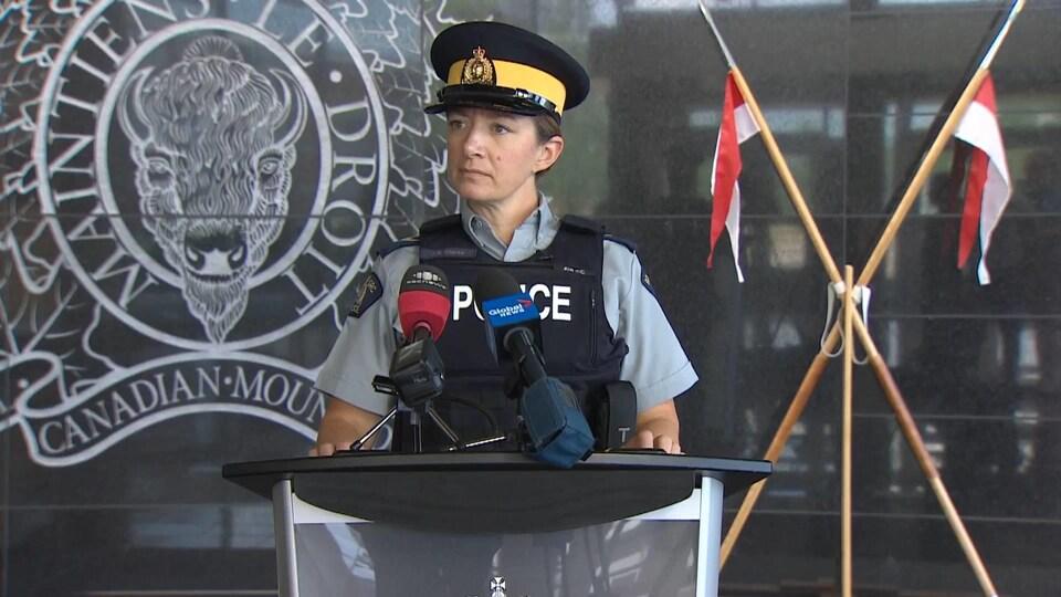 Jennifer Clarke en uniforme au podium devant des micros.
