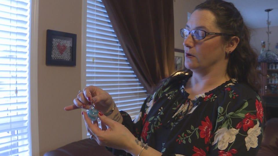Jennifer Marshall est debout dans sa maison. Elle tient une boule en verre bleue et grise faite avec les cendres du lapin familial Camper qui est mort en octobre.