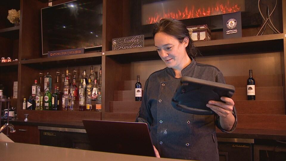 Une femme qui tient une tablette dans un restaurant.