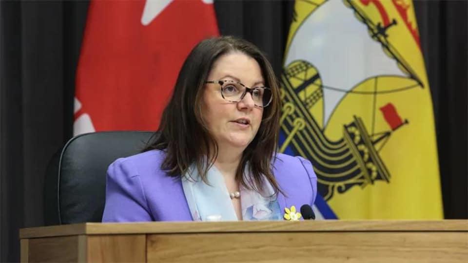 Jennifer Russell assise devant un drapeau du Nouveau-Brunswick.