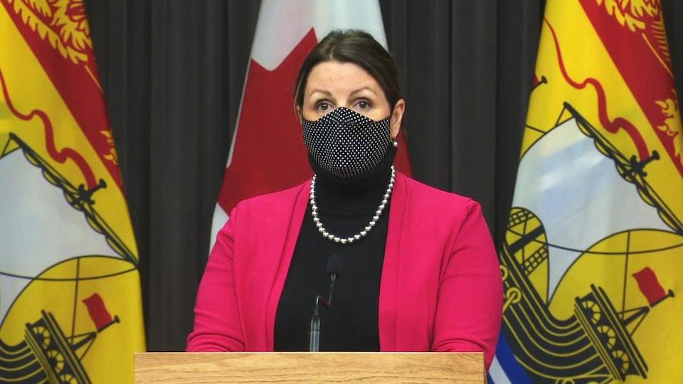 Jennifer Russell portant un masque en conférence de presse.
