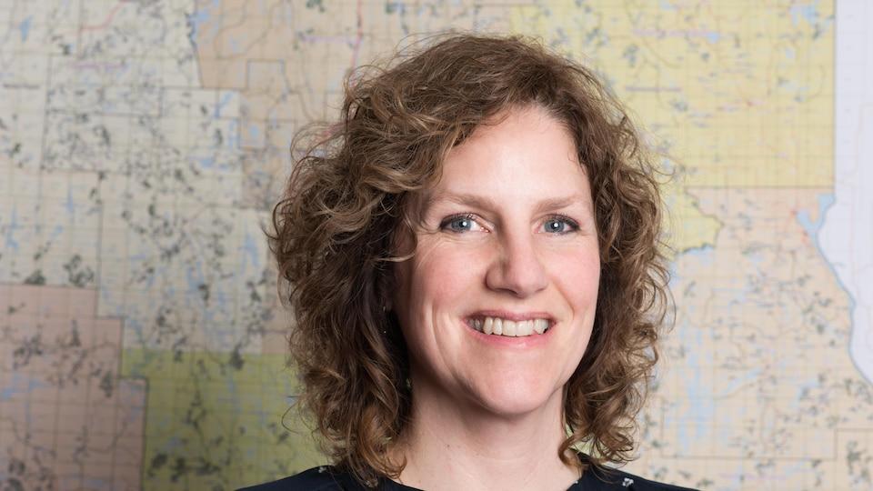 Portrait d'une femme devant une carte géographique.