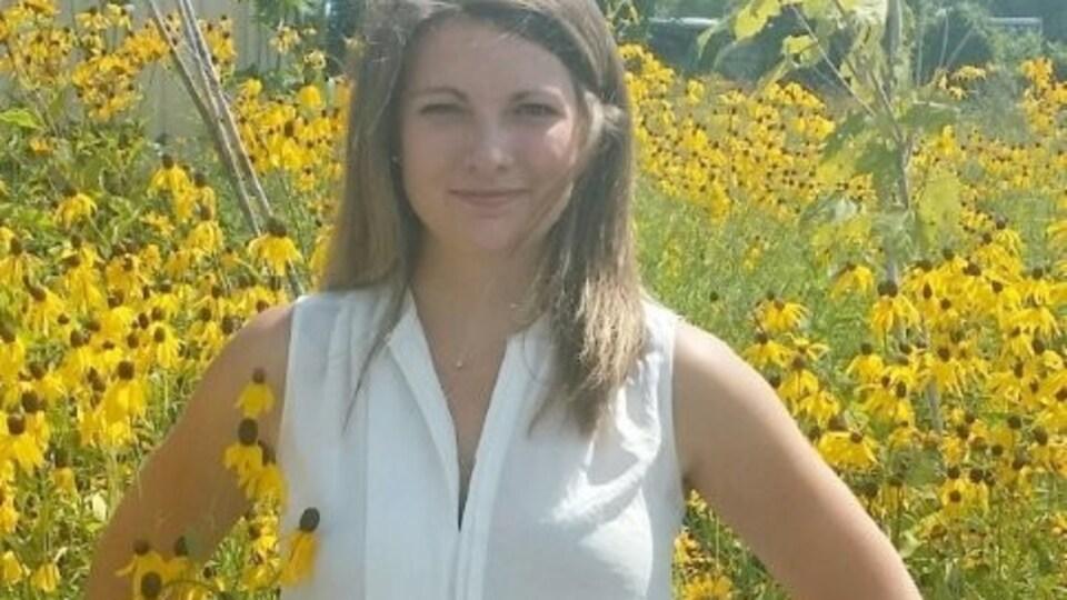 Jenny Fortier regarde la caméra alors qu'elle pose dans un champ de fleurs jaunes