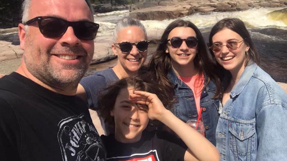 Une famille pose près d'une rivière.