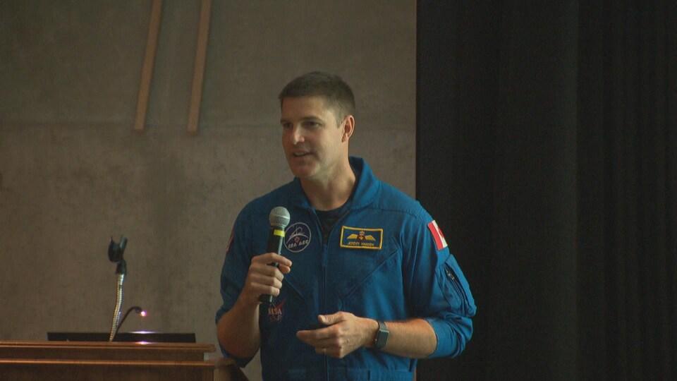 Jeremy Hansen, micro en main, donne une conférence dans le Musée de la nature.