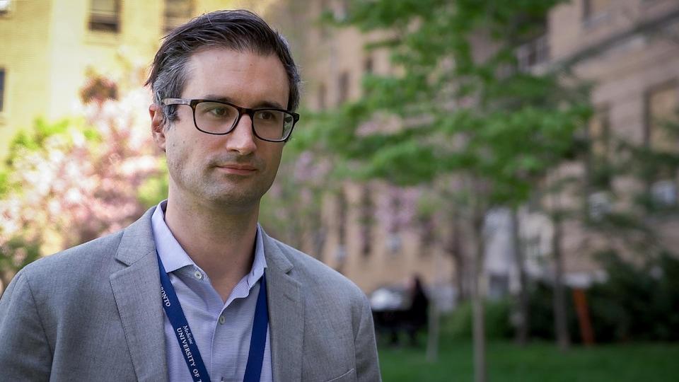 Un homme avec un badge répond en entrevue avec Radio-Canada devant l'hôpital où il travaille.