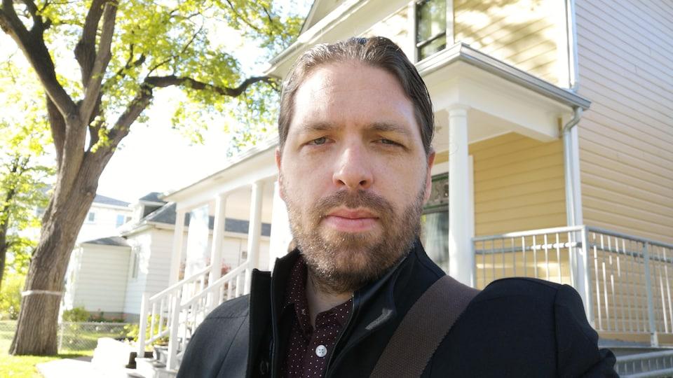 Portrait de Jérôme Melançon. Il est dehors devant une maison. Il y a un arbre à sa gauche.