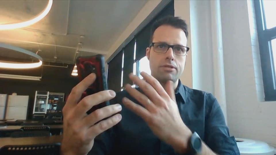 Un homme tient un téléphone cellulaire dans ses mains.