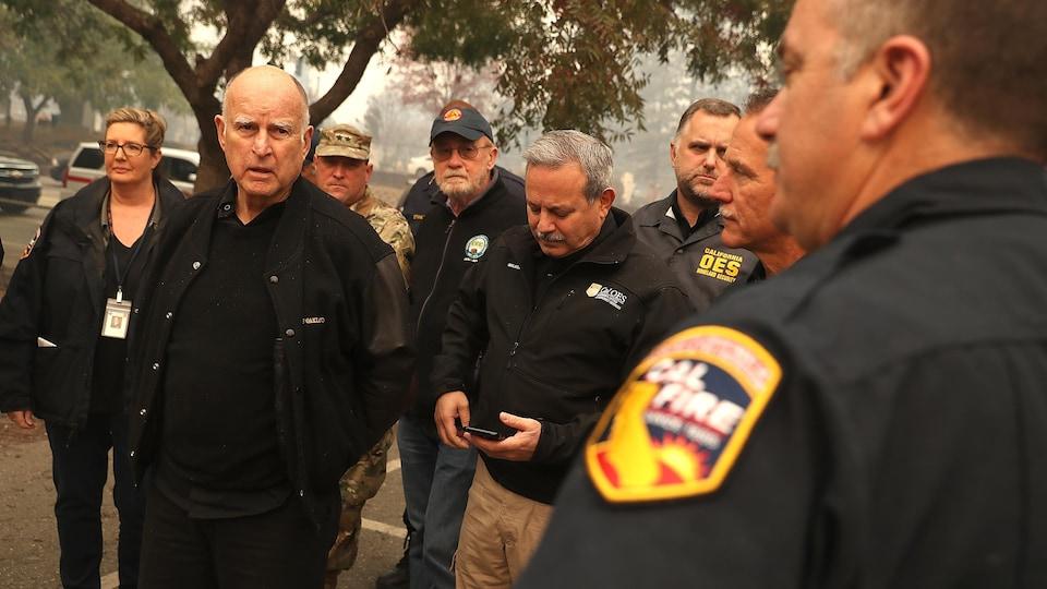 Le gouverneur de la Californie, Jerry Brown, entouré de victimes, de pompiers et de forces de l'ordre, visite la ville de Paradise après le passage de l'incendie Camp Fire.