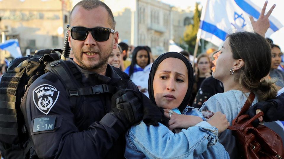 Une femme est arrêtée par un policier au milieu d'une manifestation.