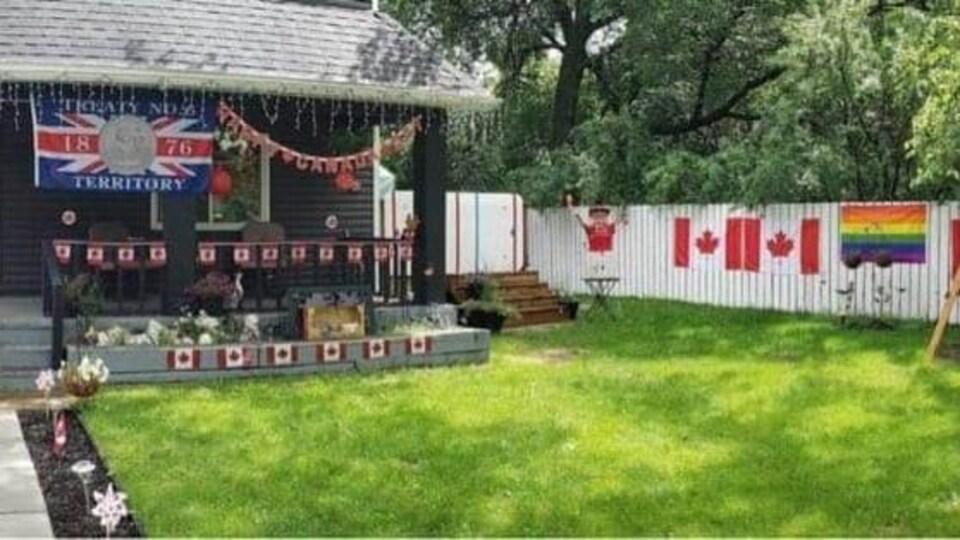 La cour avant d'une maison est décorée de drapeaux canadiens et de guirlandes. Un drapeau du Traité 6 est suspendu sous le porche. Un drapeau de la Fierté est apposé sur une clôture.