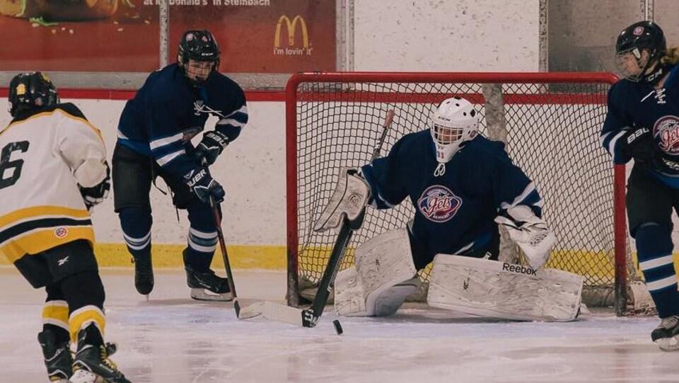 Quatre personnes jouent au hockey, le gardien bloque le but.