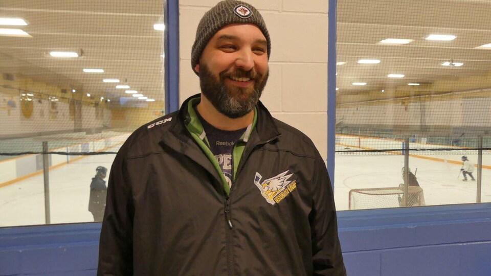 Ken Lotocki, portant une tuque des Jets de Winnipeg, dans un aréna sourit à la caméra.