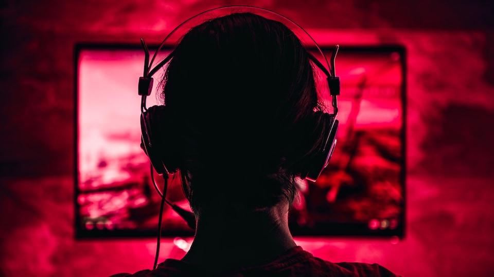 Une personne avec des écouteurs et un micro devant un écran.