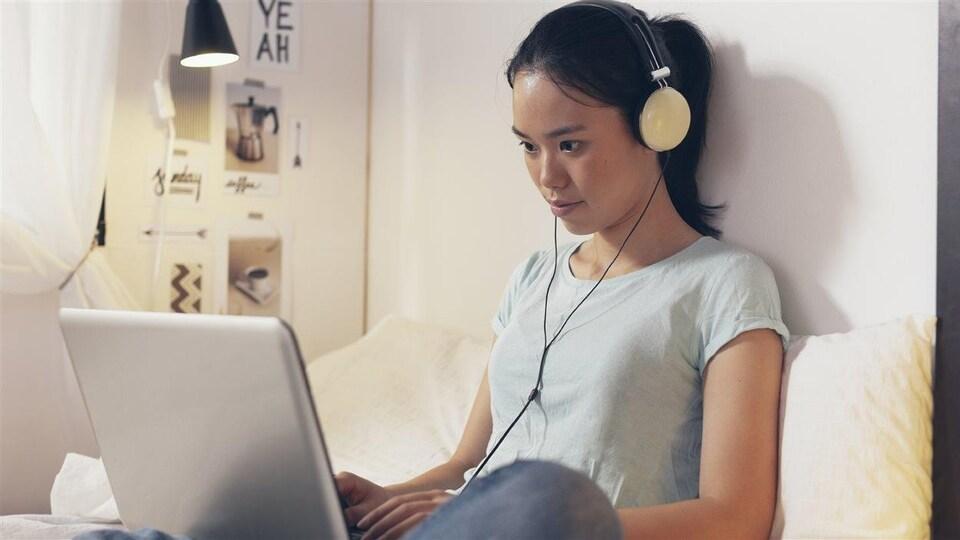 Une jeune fille est assise sur un lit, ordinateur portable sur les genoux et écouteurs sur les oreilles.