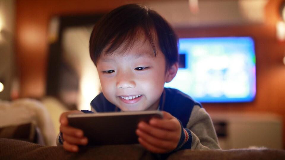 Un jeune garçon regarde l'écran d'un téléphone.