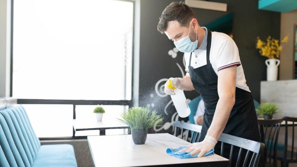 Un jeune serveur nettoie une table.