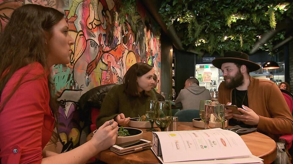 Trois personnes mangent un repas dans un restaurant, avec une grande peinture sur le mur derrière eux.