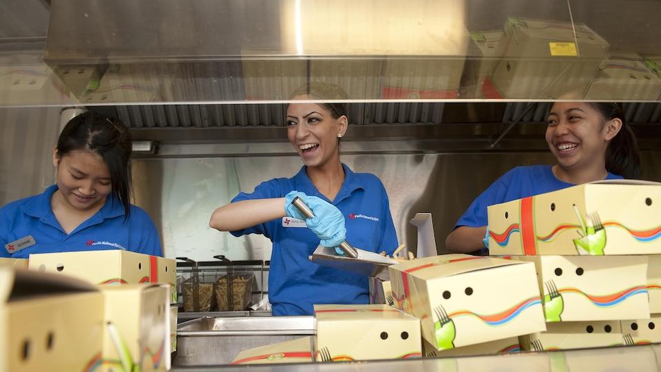Trois jeunes femmes sourient en travaillant.