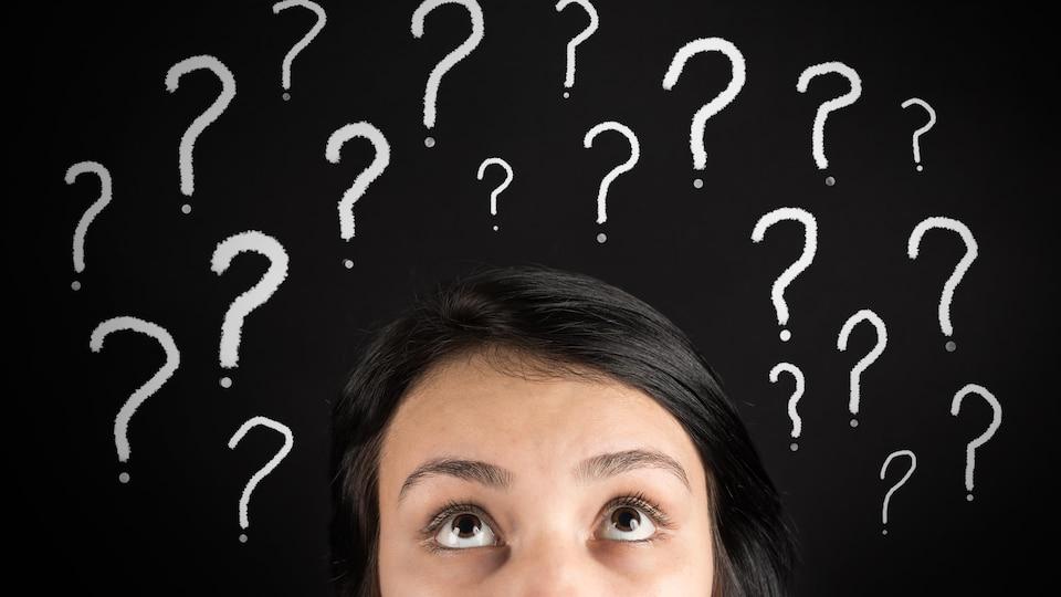 Une jeune femme confuse et des points d'interrogation.